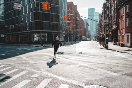 Photo for Strong man runner training and running through urban streets. Athlete prepearing for marathone on New Your streets - Royalty Free Image
