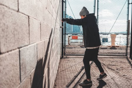 Photo for Male athlete boxing against the wall in big urban city. Sportsman training boxing in urban gateway - Royalty Free Image