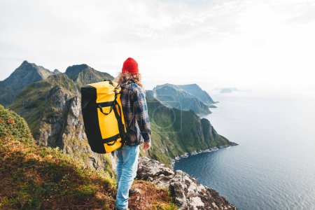 Photo for Man wearing professional backpack traveling alone on the high mountains. Traveler standing on the edge cliff rock above sea and enjoying epic view - Royalty Free Image