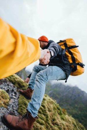 Photo pour Deux voyageurs courageux grimpent pour s'entraider. Touriste avec sac à dos aidant son ami à grimper à la montagne. Vertical - image libre de droit