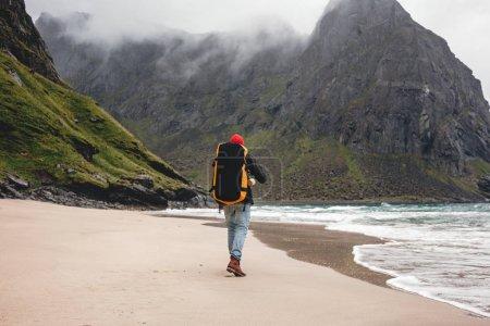 Photo pour Vue arrière de l'homme touriste avec sac à dos marchant en face du massif montagneux tout en voyageant par la plage de l'océan. Seul voyageur randonnée en plein air paysage par sable de mer - image libre de droit