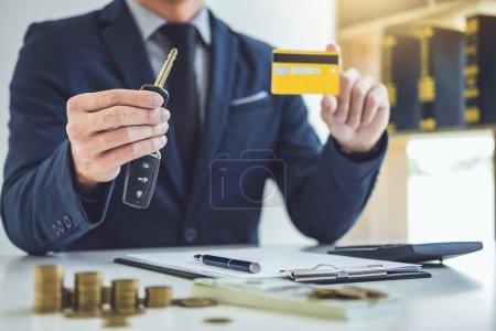 Photo pour Vendeur détenant une clé, carte de crédit et calcul d'un prix de vente de voiture neuve et prêt à domicile, concept de transport et de propriété . - image libre de droit