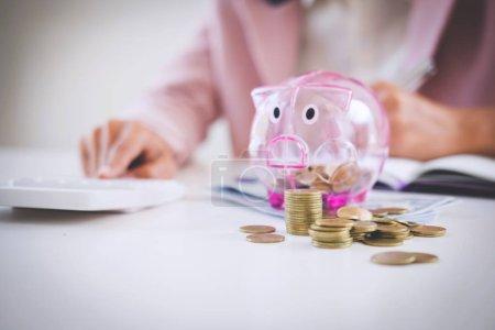 Photo pour Femme d'affaires mettre des pièces de monnaie dans une tirelire, écrire pour rapporter et utiliser une calculatrice pour analyser la stratégie d'investissement de l'entreprise avec le revenu de pièces de monnaie et de dollars, concept financier . - image libre de droit