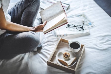Photo for Young woman happiness on bedroom in enjoying reading books and newspaper in holiday with morning coffee, relaxation and recreation concept. - Royalty Free Image