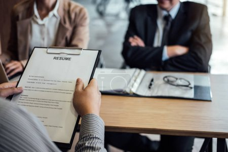 Photo for Business man holding his resume and explaining about his profile to two senior manager sitting in during job Interview. - Royalty Free Image
