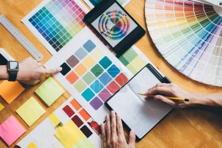 Photo for Young creative team having a meeting in creative office, Architectural drawing with work tools and accessories, Color swatch samples chart for selection coloring. - Royalty Free Image