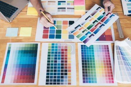 Photo pour Jeune graphiste créatif utilisant une tablette graphique pour choisir le nuancier d'échantillons de couleur pour la coloration de sélection avec des outils de travail et des accessoires sur le lieu de travail . - image libre de droit
