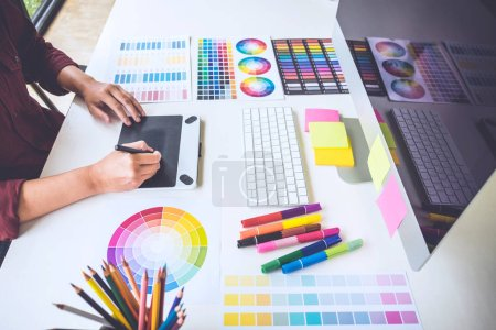 Photo for Image of female creative graphic designer working on color selection and drawing on graphics tablet at workplace. - Royalty Free Image
