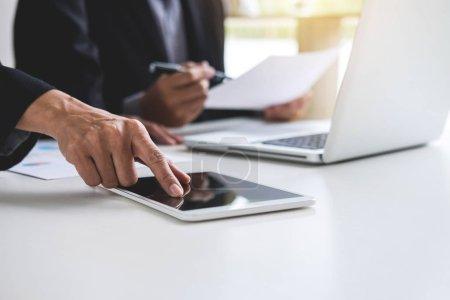 Photo pour Conférence de travail conjointe, réunion de l'équipe d'affaires présente, collègues investisseurs discutant des nouvelles données du graphique financier du plan sur la table de bureau avec ordinateur portable et tablette numérique, Finances, comptabilité, investissement . - image libre de droit