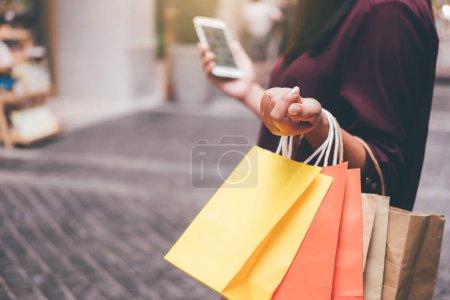 Photo pour Consommation, shopping, concept de style de vie, jeune femme tenant des sacs colorés et smartphone appréciant dans le shopping . - image libre de droit