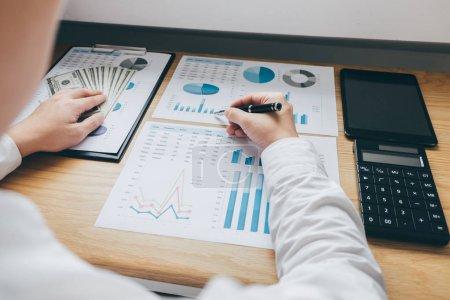 Photo pour Homme d'affaires travaillant sur un graphique document rapport financier et analyse calcul coût d'investissement avec calculatrice au bureau et d'autres objets autour . - image libre de droit