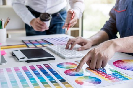 Photo for Two colleagues creative graphic designer working on color selection and drawing on graphics tablet at workplace. - Royalty Free Image