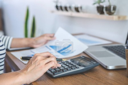 Photo for Female accountant calculations, audit and analyzing financial graph data with calculator and laptop Business, Financing, Accounting, Doing finance, Economy, Savings Banking Concept. - Royalty Free Image