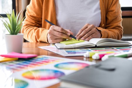 Photo for Image of female creative graphic designer working on color selection and drawing on graphics tablet at workplace with work tools and accessories. - Royalty Free Image