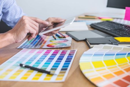 Photo for Image of male creative graphic designer working on color selection and drawing on graphics tablet at workplace with work tools and accessories in workspace. - Royalty Free Image