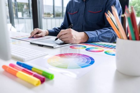 Photo pour Graphiste masculin créatif travaillant sur la sélection des couleurs et des échantillons de couleur, dessin sur tablette graphique sur le lieu de travail avec des outils de travail et des accessoires . - image libre de droit
