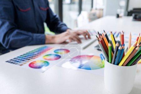 Photo pour Image de graphiste créatif masculin travaillant sur la sélection des couleurs et le dessin sur tablette graphique sur le lieu de travail avec des outils de travail et des accessoires. - image libre de droit