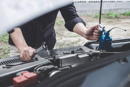 Photo for Services car engine machine concept, Automobile mechanic repairman hands repairing a car engine automotive workshop with a wrench and pouring oil, car service and maintenance. - Royalty Free Image