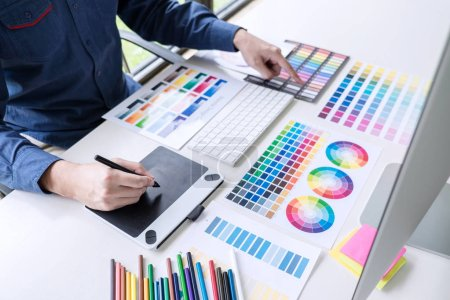 Photo for Male creative graphic designer working on color selection and color swatches, drawing on graphics tablet at workplace with work tools and accessories. - Royalty Free Image