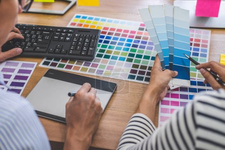 Photo for Two colleagues creative graphic designer working on color selection and drawing on graphics tablet at workplace, Color swatch samples chart for selection coloring. - Royalty Free Image