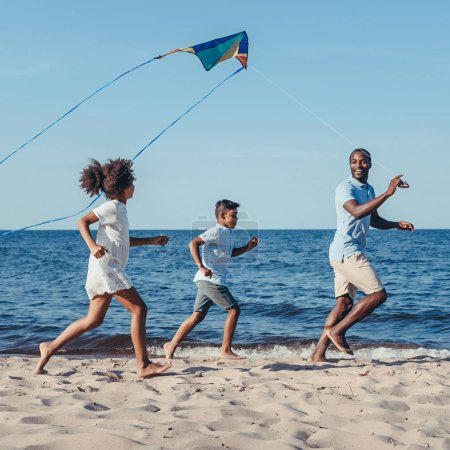 side view of happy african american father and kids playing with kite on beach