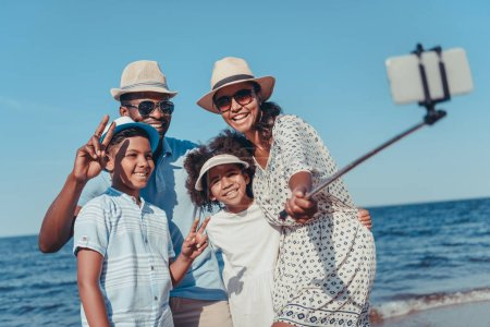 young happy african american family taking selfie with smartphone on beach on sunny day