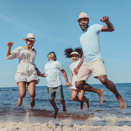 Photo for Young happy african american family holding hands and jumping on beach on sunny day - Royalty Free Image