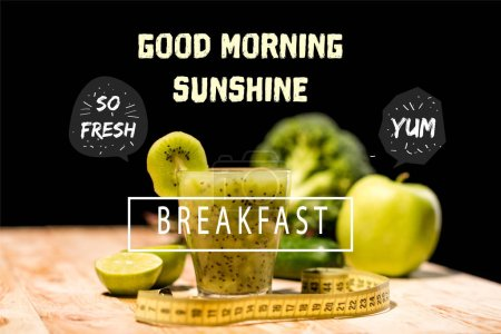 "Photo for Fresh fruit smoothie in glass with piece of kiwi, limes and measuring tape on tabletop, with ""good morning sunshine"" and  ""breakfast"" letterings - Royalty Free Image"