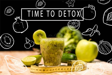 "Photo for Fresh fruit smoothie in glass with piece of kiwi, limes and measuring tape on tabletop, with ""time to detox"" inspiration with illustration - Royalty Free Image"