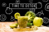 "fresh fruit smoothie in glass with piece of kiwi, limes and measuring tape on tabletop, with ""time to detox"" inspiration with illustration"