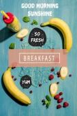 """vista superior de la botella con el batido de banana fresca y moras con hojas de menta, """"Buenos días sol"""" y """"desayuno"""" etiquetado"""