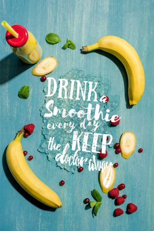 "top view of bottle with fresh banana smoothie and berries with mint leaves, with ""drink smoothie every day keep the doctor away"" lettering"