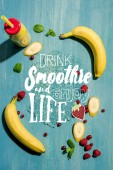 "top view of bottle with fresh banana smoothie and berries with mint leaves, with ""drink smoothieand enjoy life"" lettering"