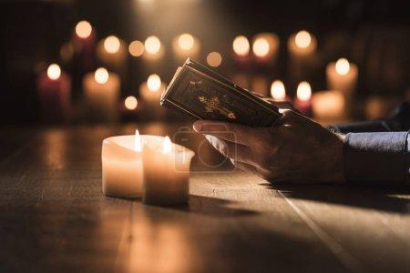 Photo pour Homme religieux lisant la Sainte Bible et priant dans l'Eglise avec des bougies allumées, concept de religion et de foi - image libre de droit