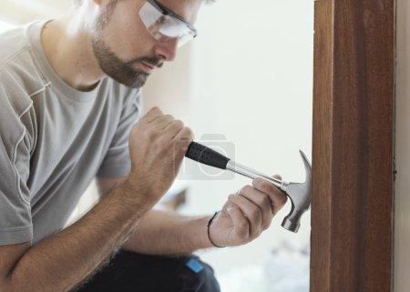 Photo pour Menuisier professionnel enlever une vieille porte à la maison: maison concept relooking et rénovation - image libre de droit