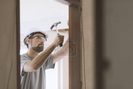 Photo pour Menuisier professionnel installer un jambage de la porte, la rénovation et la menuiserie concept - image libre de droit