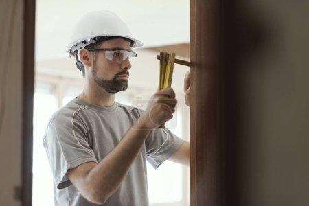 Photo pour Menuisier prenant des mesures avec une règle pliante : concept de rénovation et de construction domiciliaire - image libre de droit
