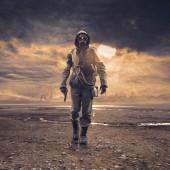 """Постер, картина, фотообои """"Храбрый солдат с противогаз и пистолет, ходить в загрязненных пост атомной пейзаж с токсичными смога и облака: экологической катастрофы и Апокалипсис концепции"""""""