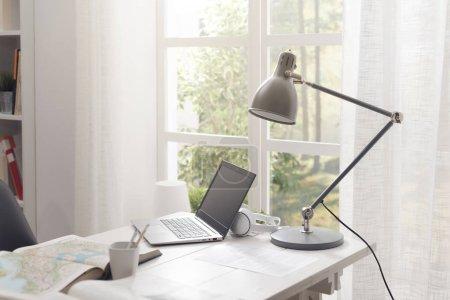 Photo pour Chambre étudiante moderne avec bureau et ordinateur portable, fenêtre en arrière-plan - image libre de droit