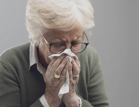 Photo pour Femme âgée malade qui se mouche, elle a le rhume et la grippe - image libre de droit