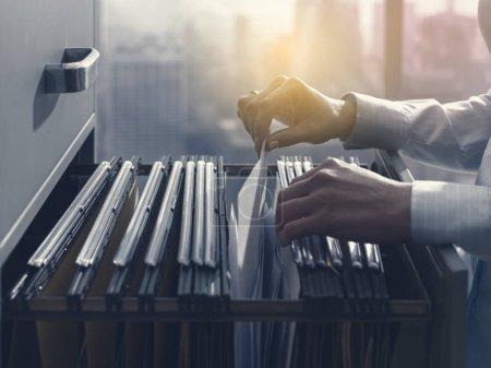 Photo pour Commis aux employées de bureau professionnel, la recherche de fichiers et la paperasserie dans le classeur - image libre de droit