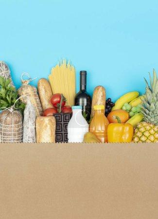 Foto de Gran bolsa de compras con una variedad de productos frescos de alimentación: verduras, frutas, bebidas y carne curada - Imagen libre de derechos