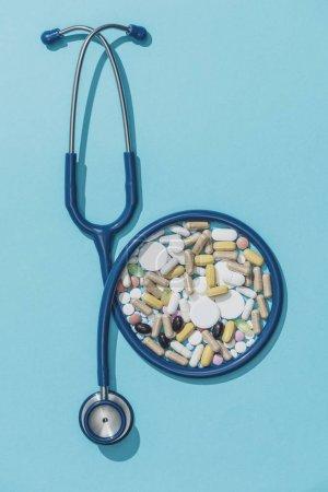 Foto de Estetoscopio médico y una gran cantidad de píldoras y cápsulas: medicina de prescripción y concepto de abuso de drogas - Imagen libre de derechos