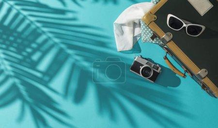 Foto de Embalaje para vacaciones en verano: maleta, gafas de sol, cámara y hojas de palma tropical sombra, espacio de copia en blanco - Imagen libre de derechos