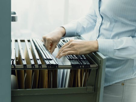 Professional female office clerk searching files a...