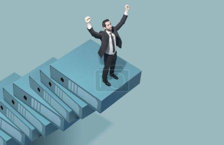 Foto de Empresario corporativo escalando la escalera del éxito: está con los puños levantados y celebrando, ganando el concepto de negocio - Imagen libre de derechos