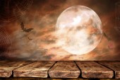 empty wooden table with creepy Halloween background