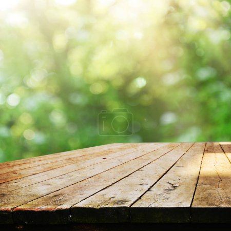 Empty wooden table with blurred natural background