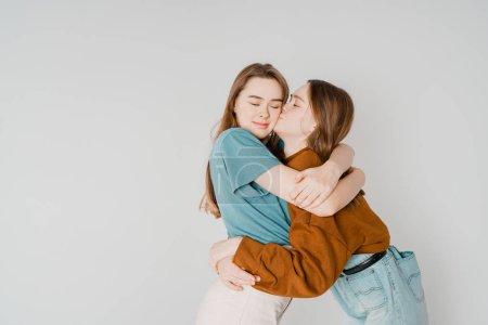 Photo pour Deux sœurs jumelles belles filles hipsters en vêtements décontractés sur fond gris isolé, concept amour, amitié, âmes sœurs - image libre de droit