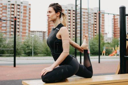 Photo pour Attrayant jeune femme en forme dans le sport gris porter le faire échauffement étirement avant l'entraînement sur la zone d'entraînement de rue. Le mode de vie sain dans le concept de la ville - image libre de droit